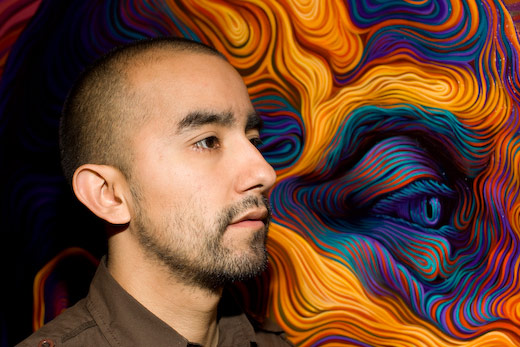 Painter and muralist Vincent Valdez stands beside one of his stunning works of art. Courtesy photo.