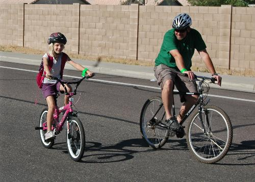 Bike to school day. A father rides with his helmeted daughter to school. Photo: www.pedbikeimages.org /Mike Cynecki