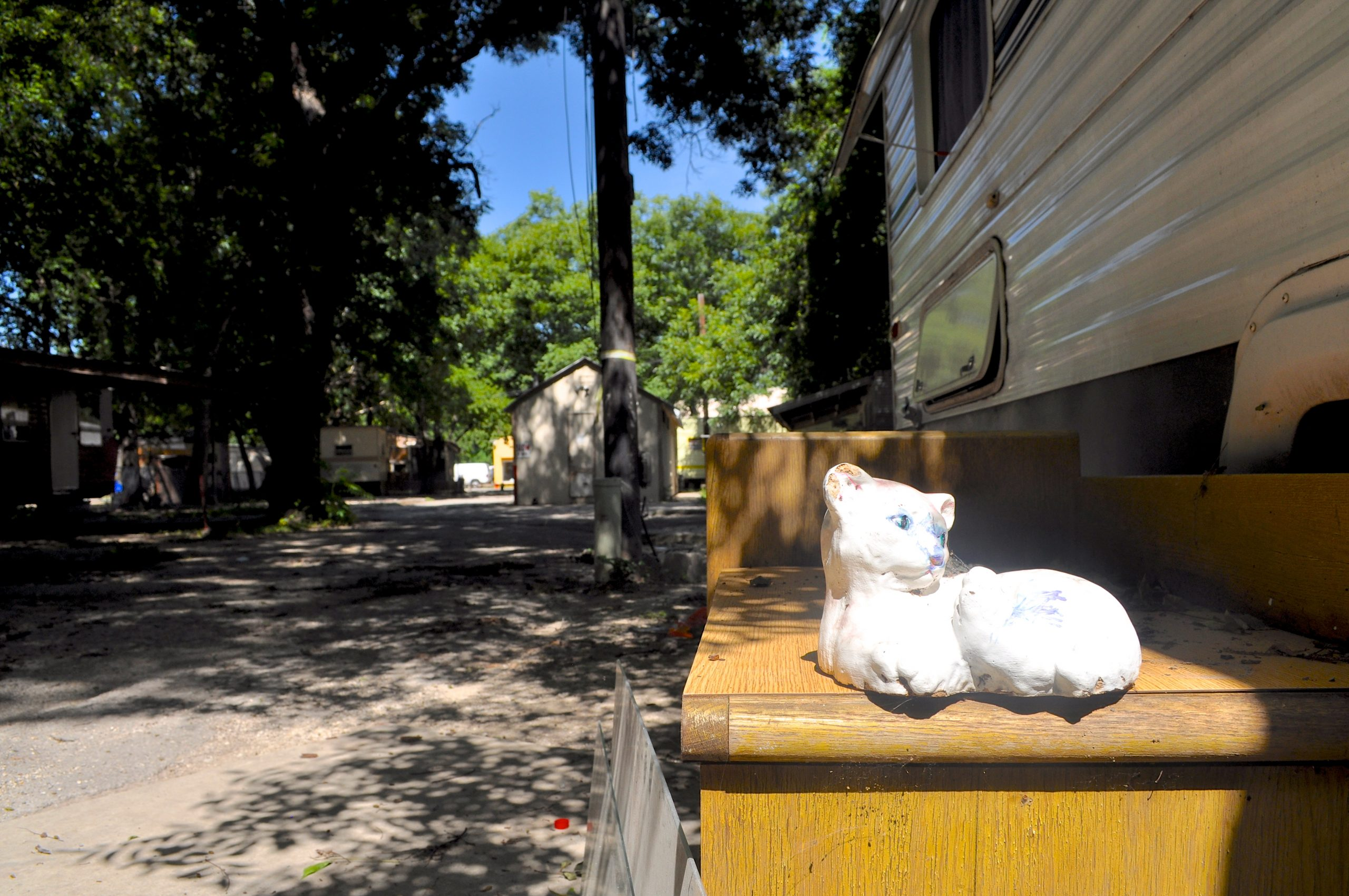 A ceramic cat lies in wait for its abandoned trailer owners at the new Roosevelt Avenue development site. Photo by Iris Dimmick.
