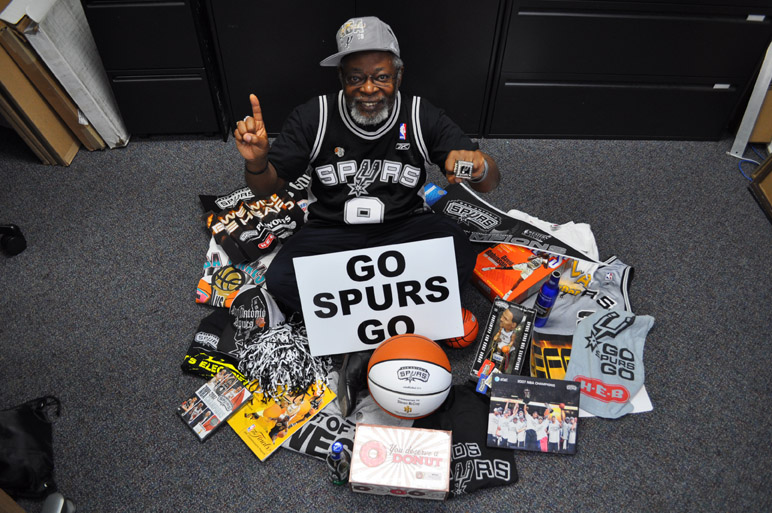 Steve McCray, a retired Air Force master sergeant and graphic artist for the Air Force Recruiting Service Marketing Division, is the ultimate Spurs fan. Here he's surrounded by just a small portion of his Spurs memorabilia. The box of doughnuts is representative of the approximately 40 dozen doughnuts he's bought over the years after every playoff win. Photo by Annette Crawford.