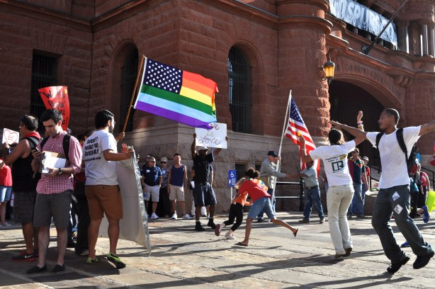 Revelers gather in front of the Bexar County Courthouse to celebrate the Supreme Court decision finding DOMA and Prop 8 unconstitutional. Photo by Iris Dimmick.
