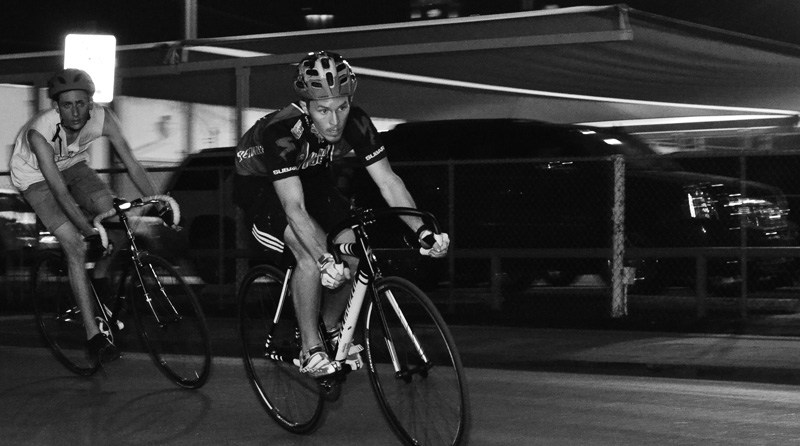 Racers round a corner while riding during an underground, nighttime bike criterium (a short, timed route – winner makes the most laps). Photo by David Rangel.