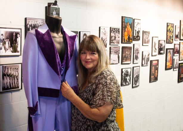 STPCC Co-Founder Michael Ann Coker poses for a photo next to a lavender tuxedo that Sunny Ozuna, a popular ____ singer, performed in. Photo by Garrett Heath.