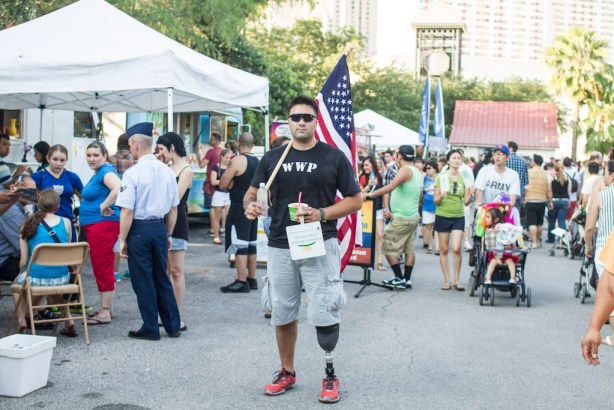 Derrick proudly carries a large U.S. flag through the crowds at Hemisfair Park's Fourth of July celebration. Photo by Steven Starnes.
