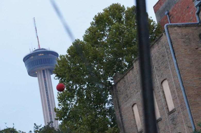 A ball, kicked by a Downtown Kickball team member soars into a field at Hemisfair Park next to the Magik Children's Theatre, the Tower of the Americas in the distance. Photo by Vanessa Mulholland.