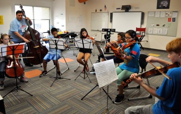 Steve Zeserman instructions young violinists at St. Mary's Hall during YOSA's 2013 summer camp. Photo by Iris Dimmick.