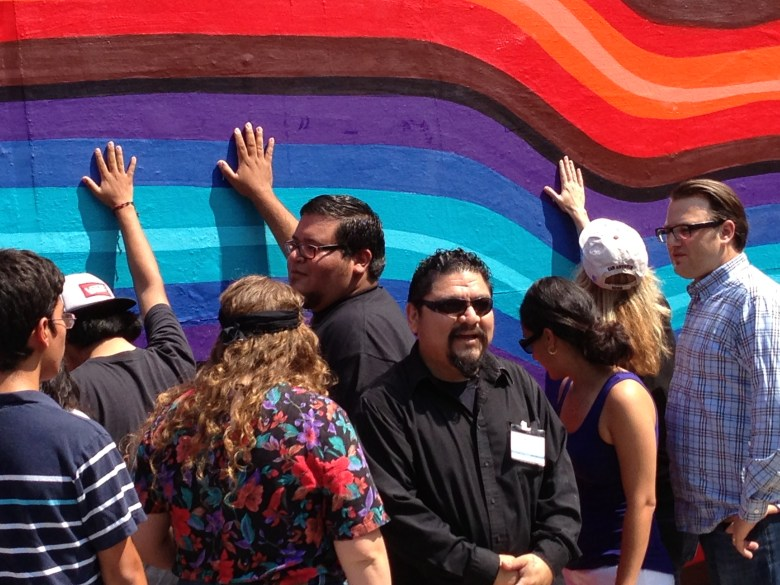 Alex Rubio and mural contributors lay hands on the mural to bless it's future in the community.