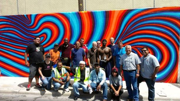 """John Medina (far left) and Harvey Mireles (second from right) with volunteers working on Alex Rubio's """"Vortex"""" mural on the Eastside. Photo by Bekah McNeel."""