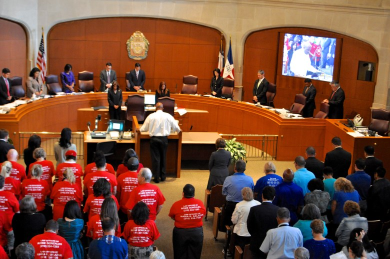 San Antonio Mayor, City Council members, citizens (those that oppose and those that support the non-dicrimination ordinance) bow their heads in prayer together before the morning session commences. Photo by Iris Dimmick.