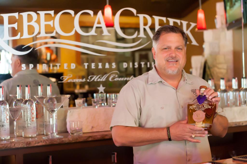 Mike Cameron holds a bottle of Rebecca Creek Texas Spirit Whiskey in the tasting room of the Rebecca Creek Distillery. Photo by Garrett Heath.