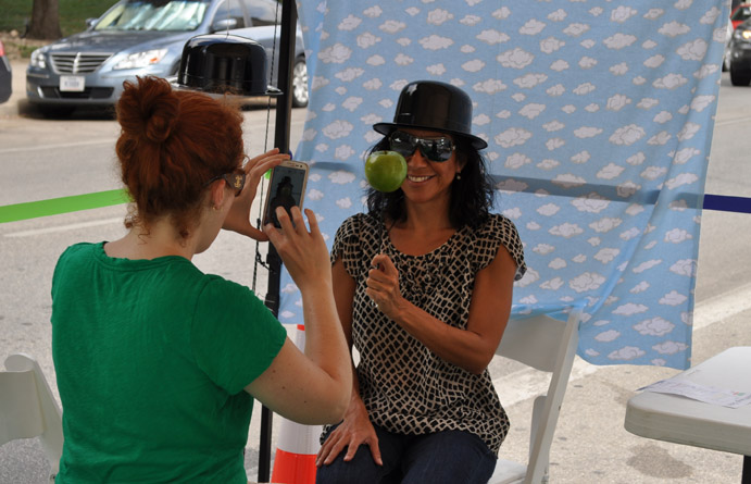 Michelle Garrigan takes a photo of a visitor to the Southwest School of Art booth. Visitors could have their photo taken with their phones while wearing the props provided by the school. They were then encouraged to upload their photos to Instagram. Photo by Annette Crawford.
