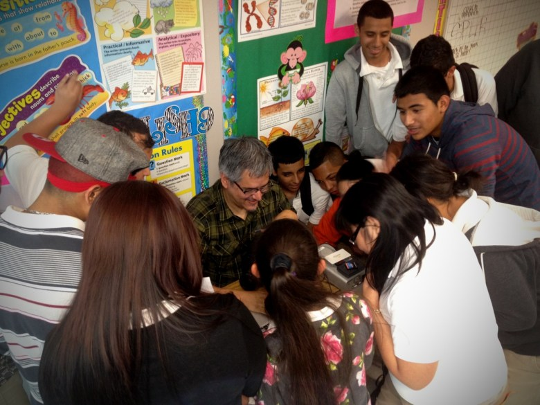 Jim Mendiola (center) shows students footage collected for his documentary about the Middle School Partners Program. Courtesy photo.