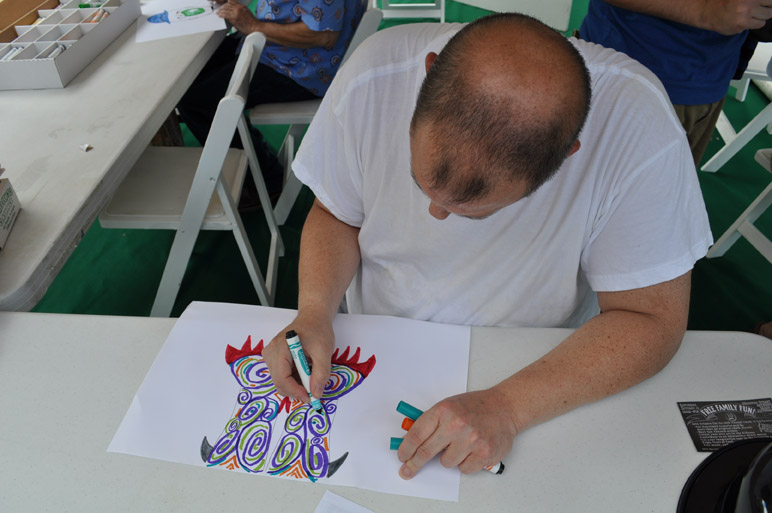 """Ed, a resident of the Robert E. Lee Apartments, draws his portion of the """"exquisite corpse"""" at the Southwest School of Art spot during PARK(ing) Day. Photo by Annette Crawford."""