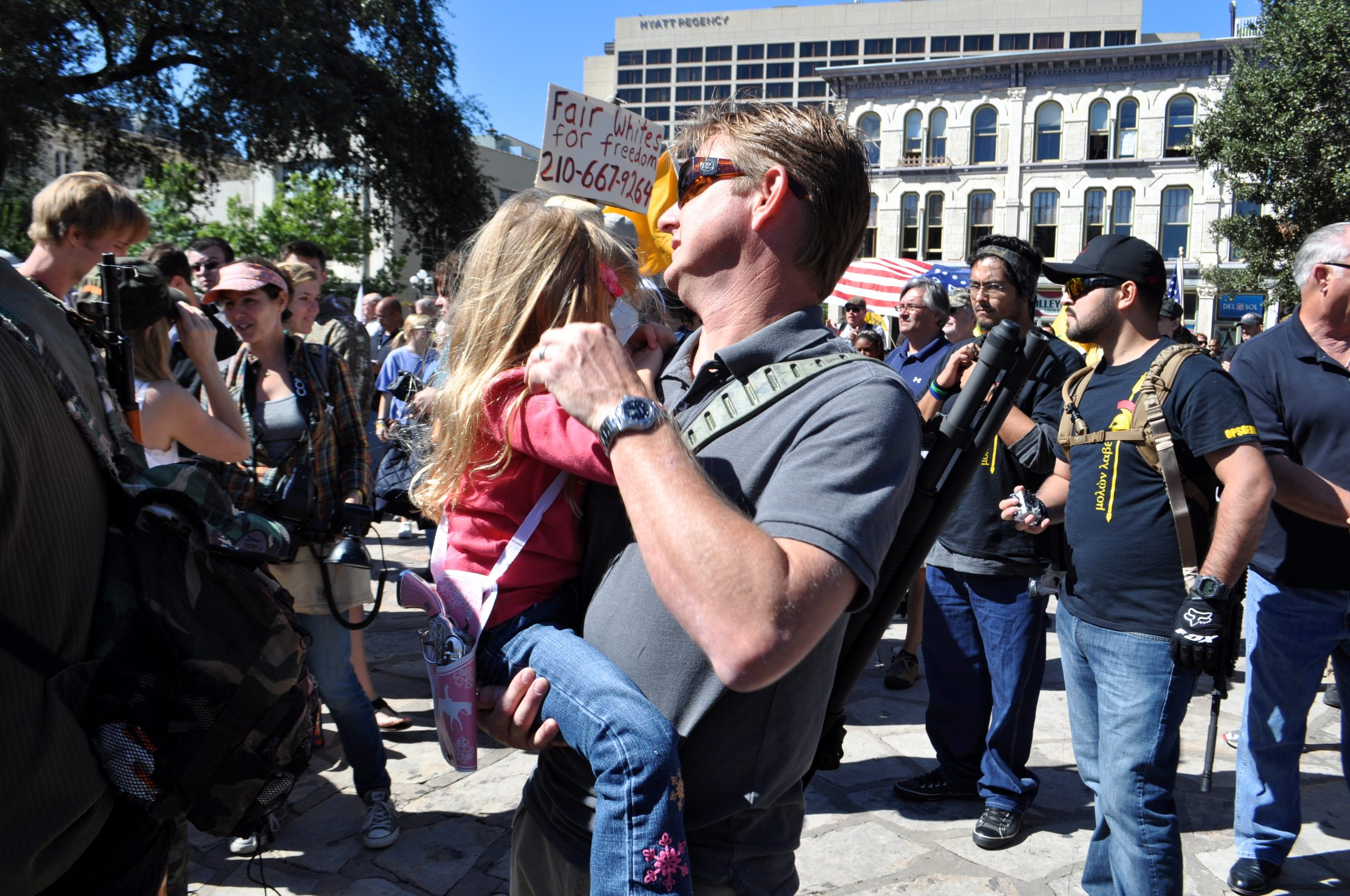Camera shy but not gun shy, a young girl gets comfortable in her father's arms at the gun rally in Alamo Plaza. Photo by Iris Dimmick.