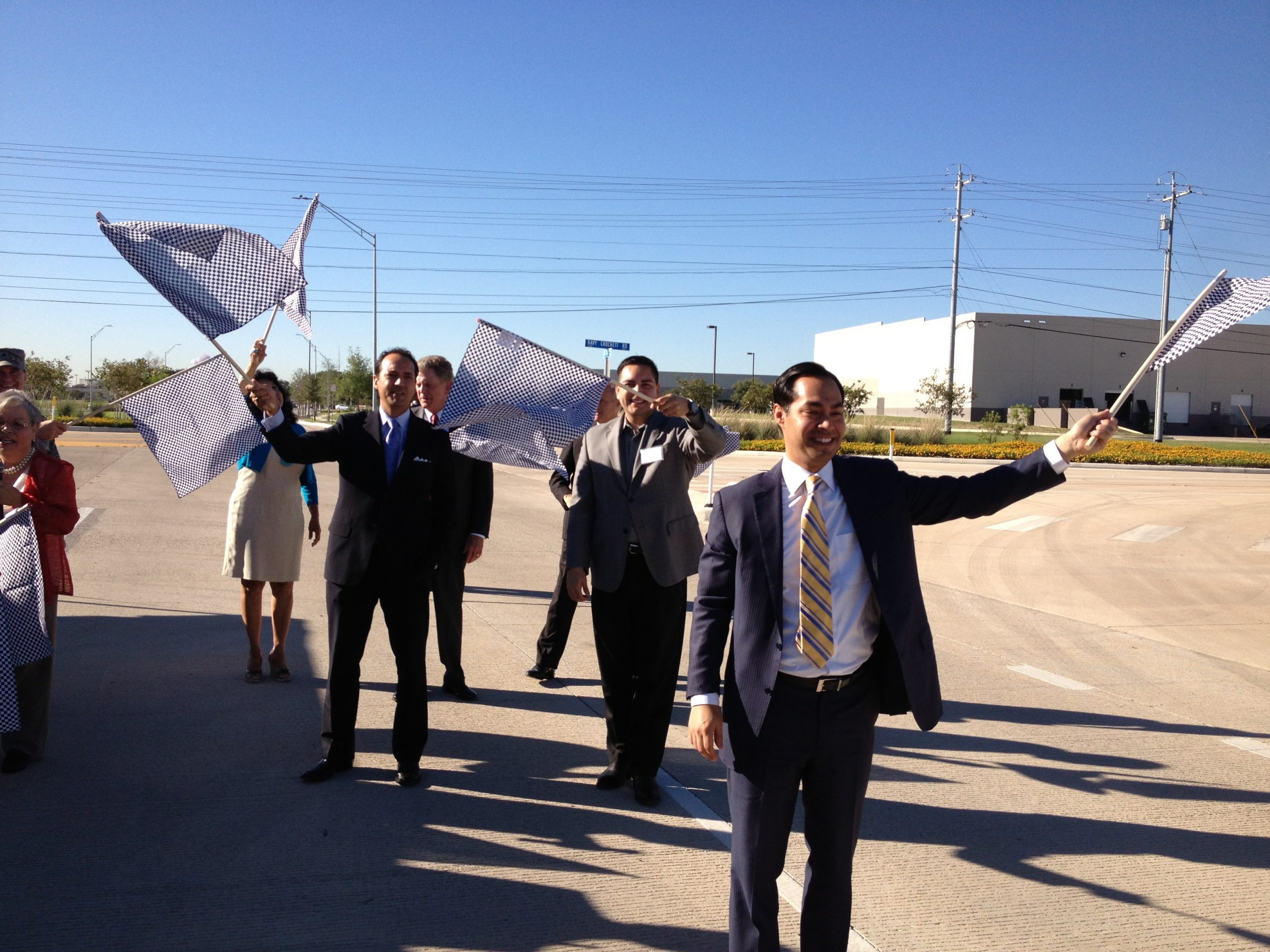 Mayor Julián Castro and crew wave flags for the first trucks on Port San Antonio's 36th Street extension. Photo by Robert Rivard.