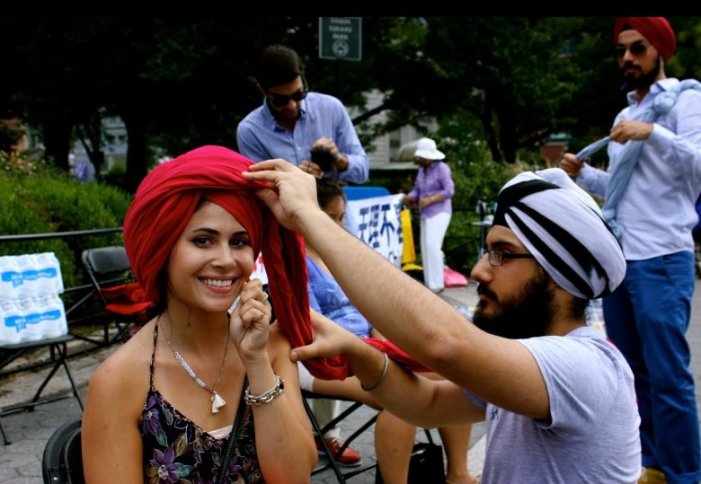 Harmann Singh of The Surat Initiative puts the final touches on a smiling New Yorker. Photo courtesy of the Surat Initiative.