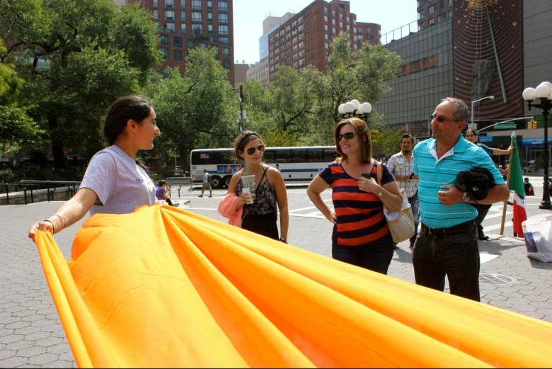 Gurbani Kaur of The Surat Initiative helps prepare a turban while speaking to visitors in NYC. The average Sikh turban is about five meters long and must be folded before being tied.