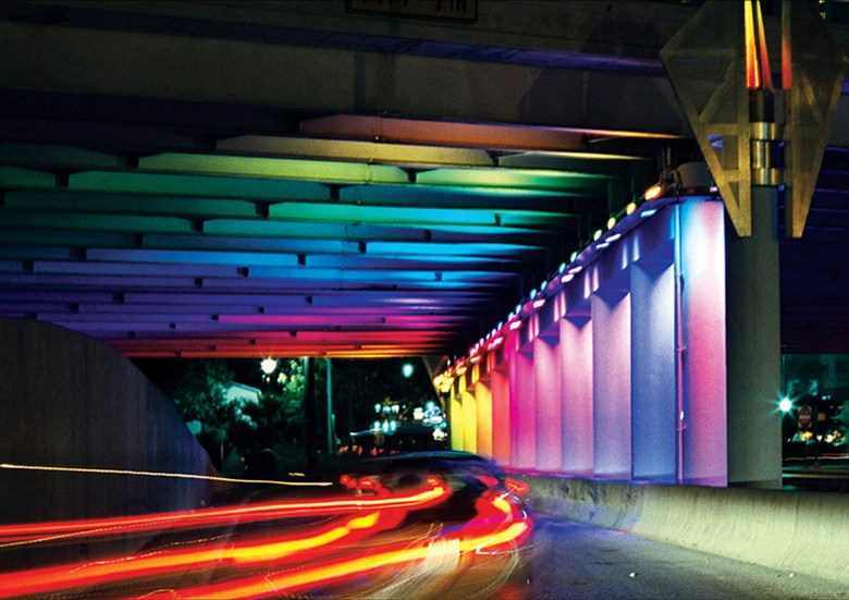 """Using two underpasses at Commerce and Houston Streets, """"Light Channels"""" illuminates a visual barrier between San Antonio's Convention Center and a shopping center that had minimal foot traffic. Light Channels encourages visitors to cross under the highway, through the barrier, opening a new flow of customers. This project was a collaboration between the City of San Antonio, the County Government, TX DOT, a downtown business association, and artist Bill FitzGibbons."""