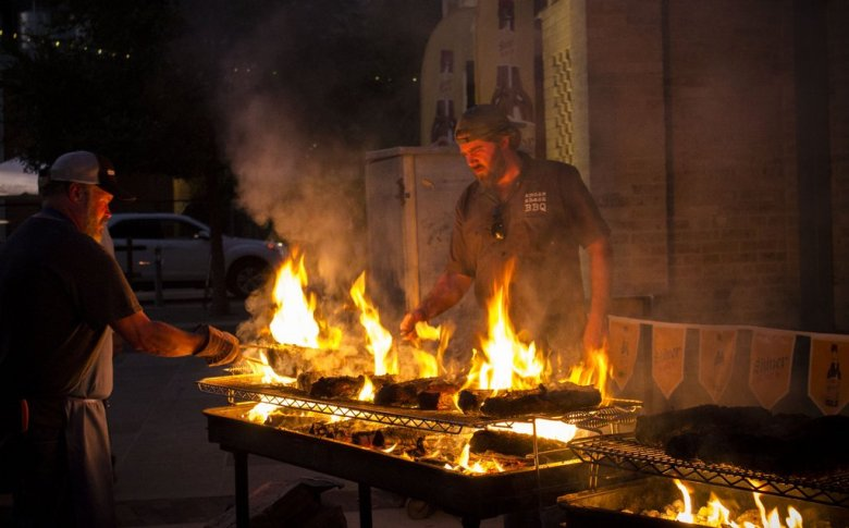 Tim Byres' sous chefs transfer meat from an intensely hot grill to a slightly cooler one to finish. Photo by Jesse Torres.