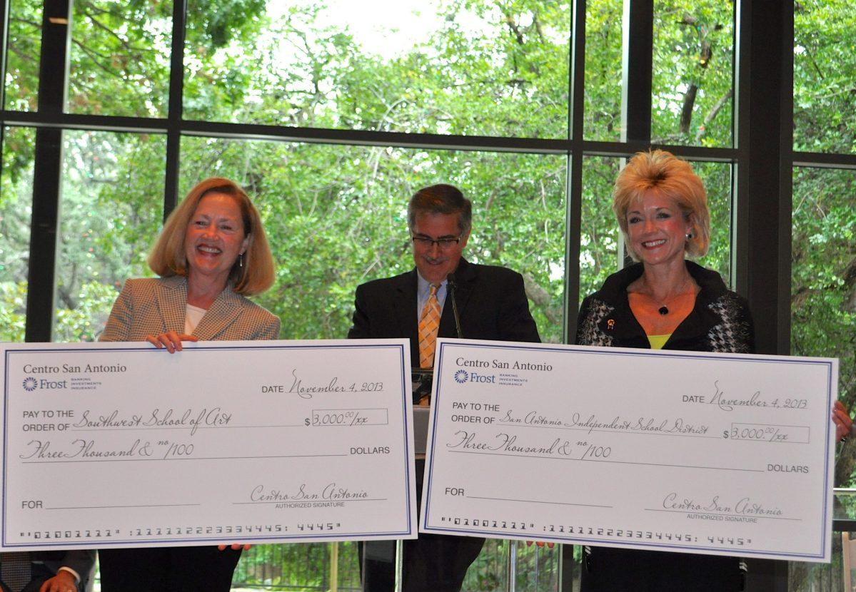 Southwest School of Art President Paula Owen (left) and SAISD Foundation Chair Carri Baker Wells accept $3,000 checks from Centro San Antonio President and CEO Pat DiGiovanni. Photo by Iris Dimmick.