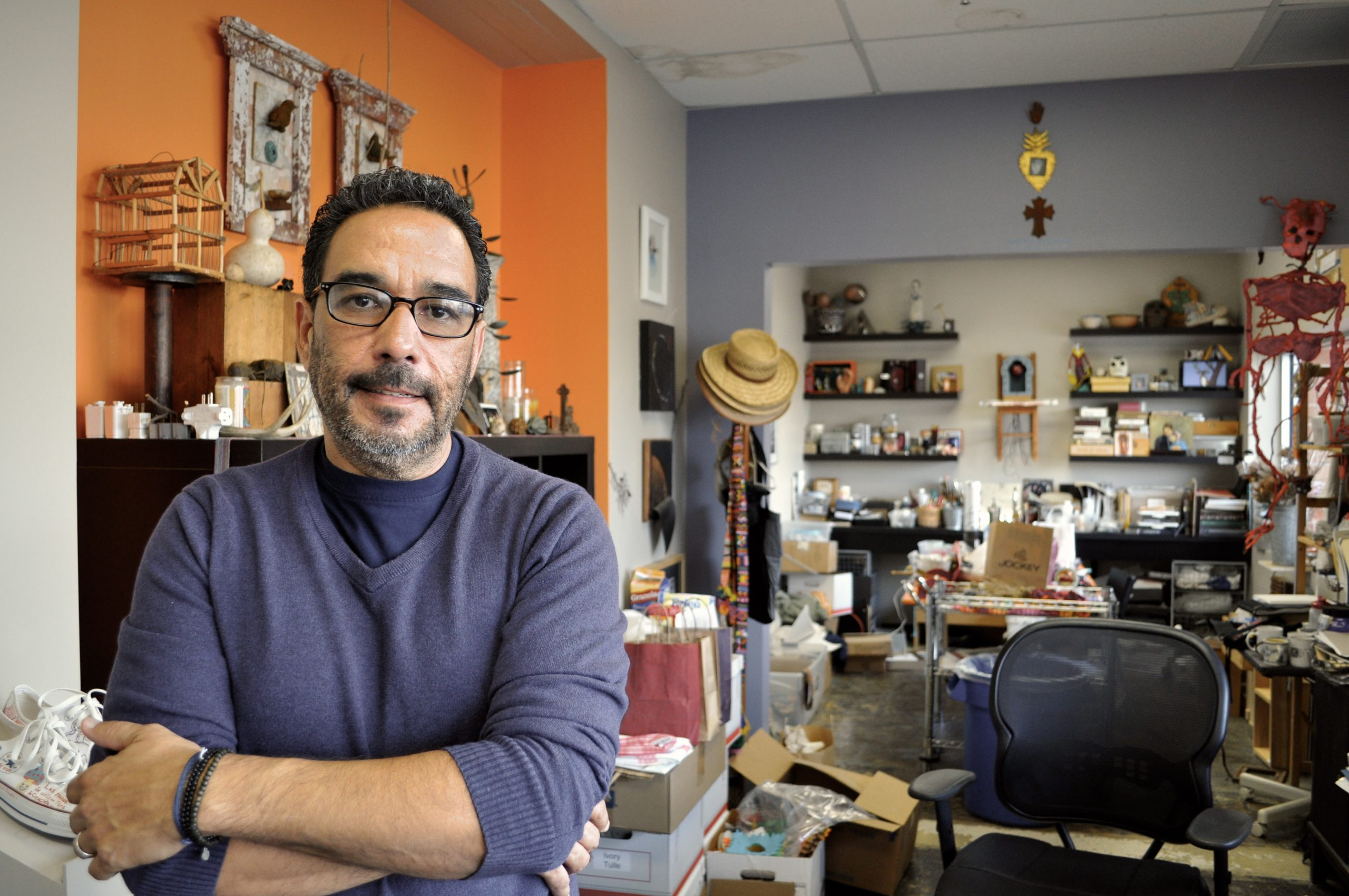 SAY Sí Executive and Artistic Director Jon Hinojosa poses for a photo in his office, which has a tendency to look more like and art studio. Photo by Iris Dimmick.