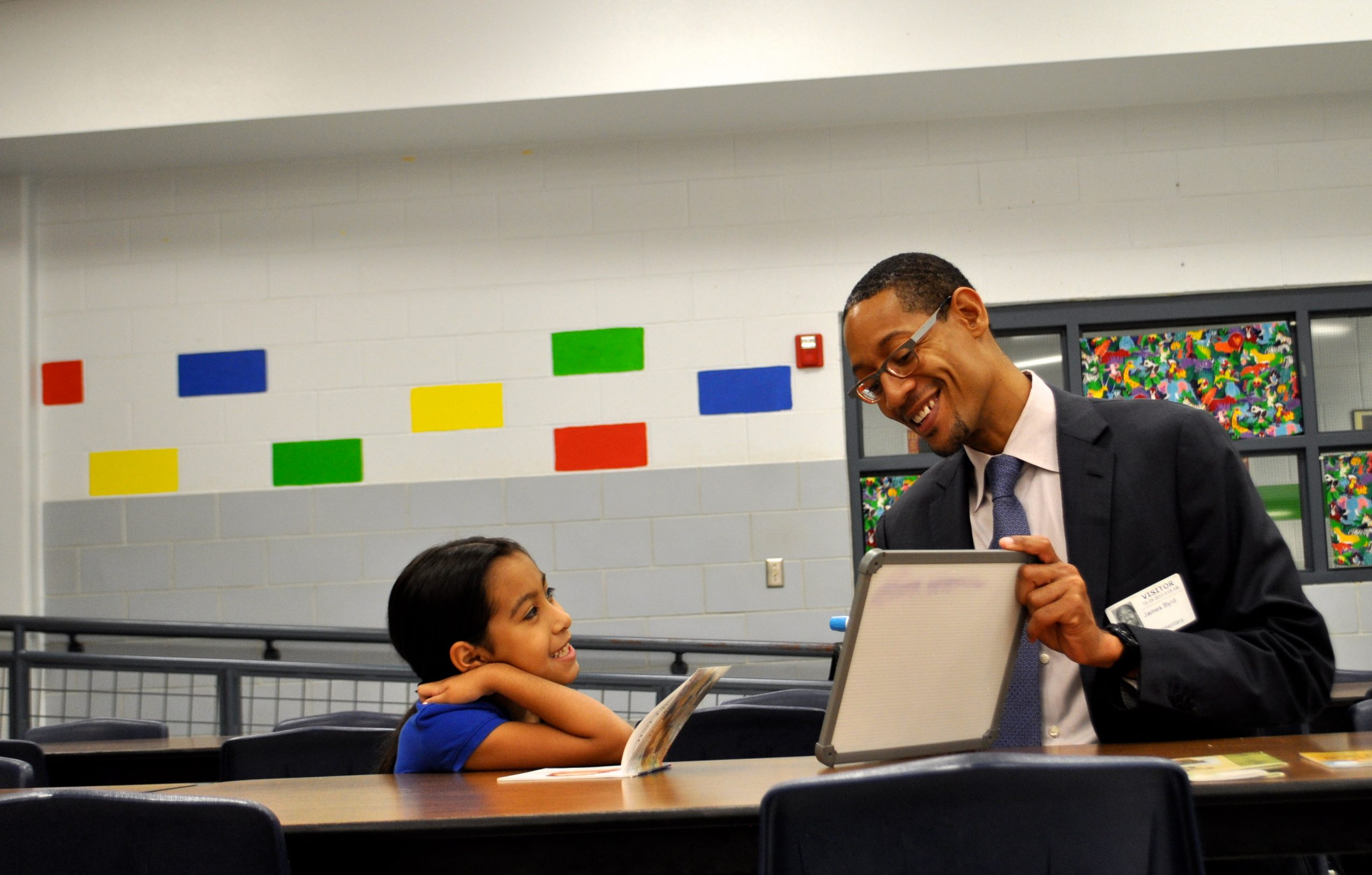 """Darryl Byrd helps Herff Elementary student, Diamond, sound out a new word (""""pancakes""""). Photo by Iris Dimmick."""