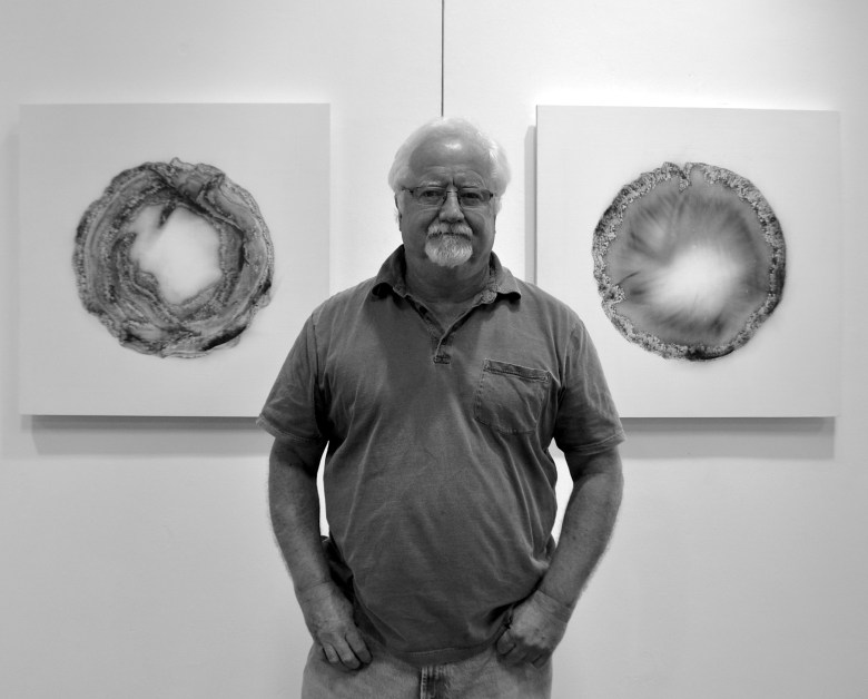 Bill FitzGibbons stands with two of his latest fire drawings. Photo by Iris Dimmick.