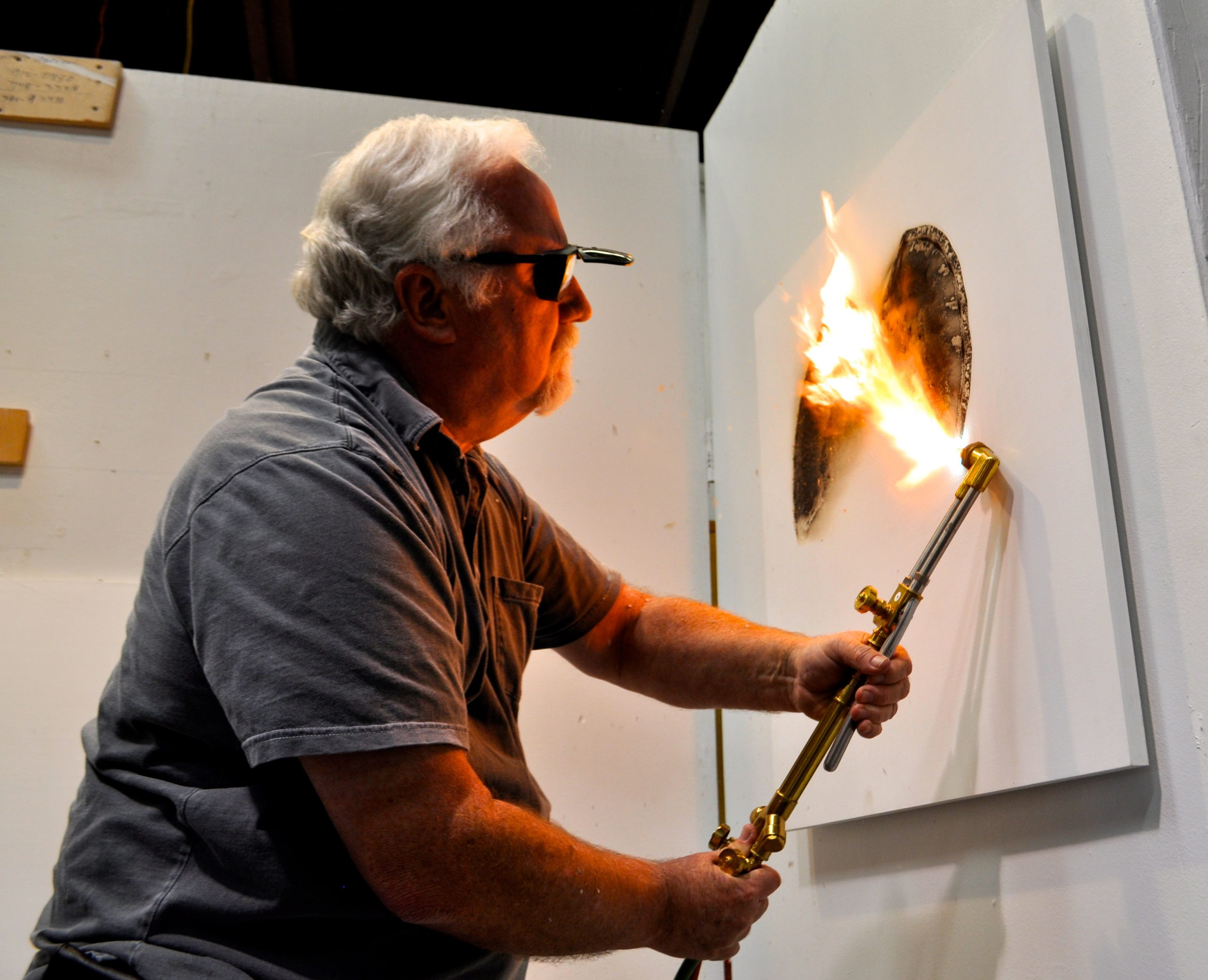 Bill FitzGibbons demonstrates his fire drawing technique, a divergence of mediums for the sculptor who usually works with large light installations. Photo by Iris Dimmick.
