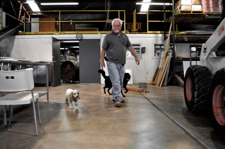 His two dogs Sheffield (left) and Lone Star follow Bill FitzGibbons through the expansive studio space. Photo by Iris Dimmick.