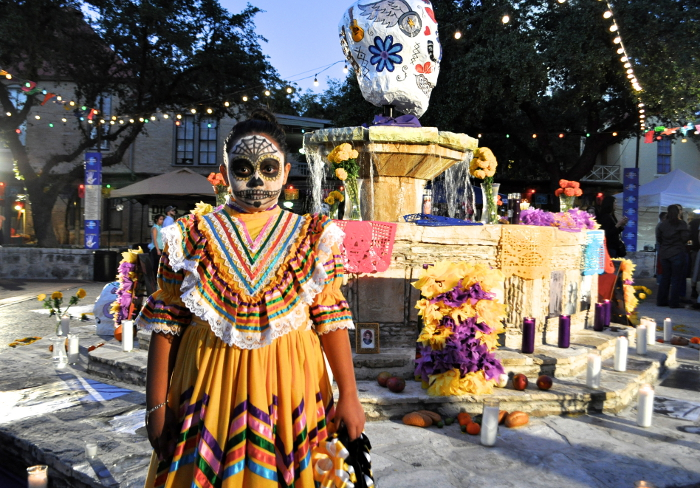 A young girl stand at the fountain in La Villita during Día De Los Muertos 2013. Photo by Iris Dimmick.