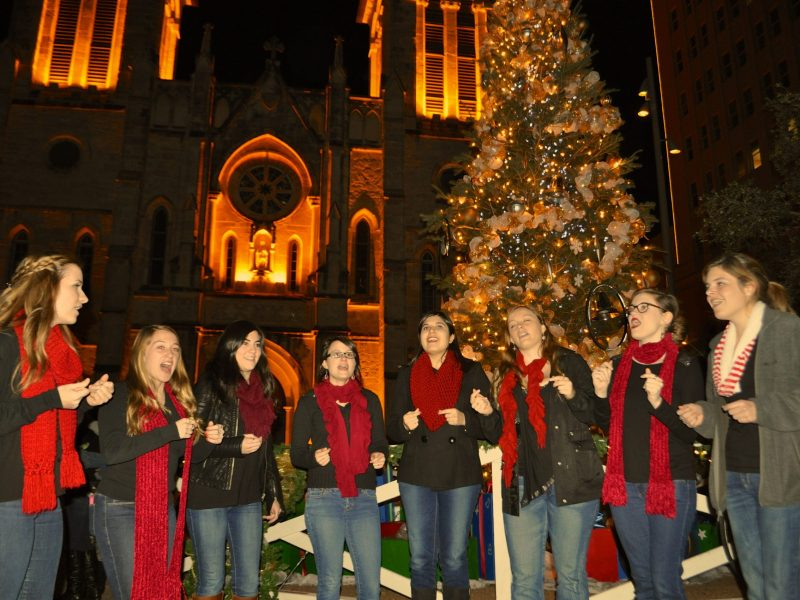 The AcaBellas of Trinity University sing holiday carols in Main Plaza for Something Monday riders. Photo by Iris Dimmick.