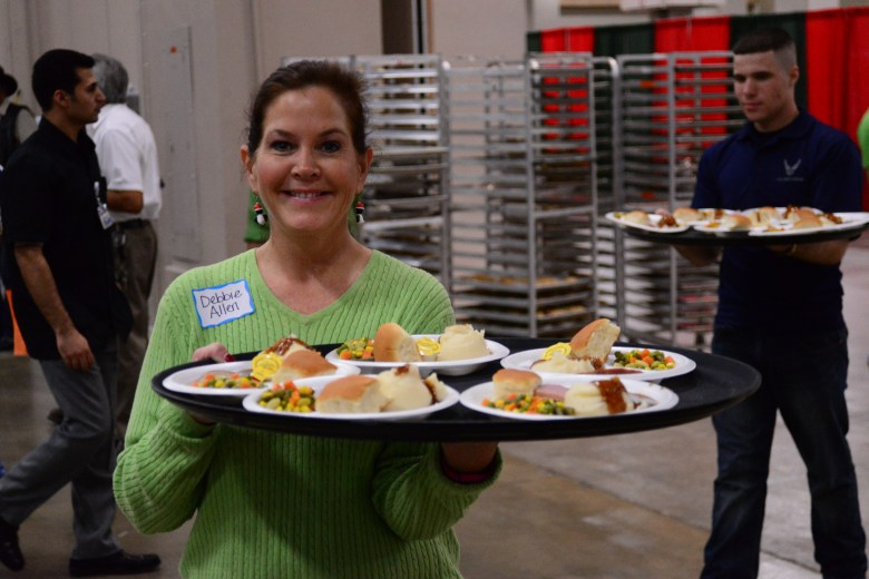 Volunteer Debbie Allen brings out yet another tray of food plates. Photo by Page Graham.