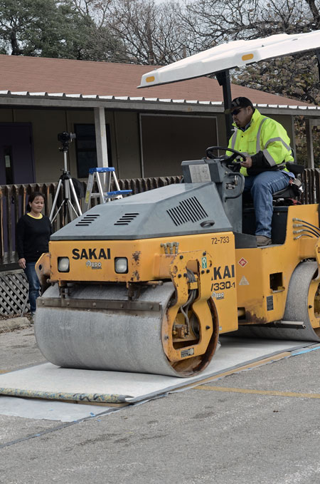 A steamroller in the parking lot of Centro Cultural Hispano de San Marcos creates a relief print by rolling over protective materials onto the sheet of paper and wooden block underneath. The machine's weight presses the ink on the carved wooden block onto the piece of paper to transfer the design.