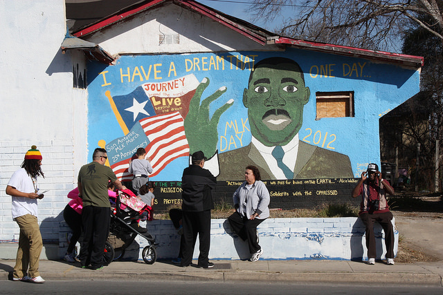 San Antonians sit next to a mural on San Antonio's Eastside that depicts Martin Luther King, Jr. Photo by Kay Richter.