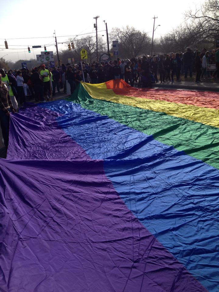 LGBT community supporters carry a large rainbow flag during the 2014 MLK Day march. David Jordan Cisneros of GetEqual Texas.