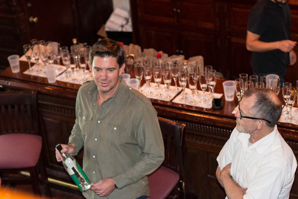 Wyatt Peabody holds an old bottle of Chinaco tequila as Tomas Estes (right) looks on. Photo by Garrett Heath.