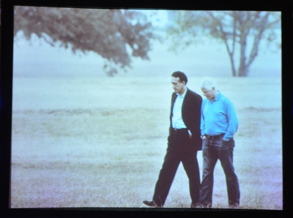 President Clinton and Henry Cisneros walk together. Photo of projected image displayed during banquet.