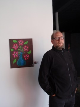 Erik Bosse poses by art in the gallery section of the new space at Fredericksburg - photo by Kevin Tobar Pesantez