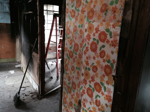 Despite the fire, the 60s-era wallpaper behind the scorched wall in the kitchen is in perfect condition.