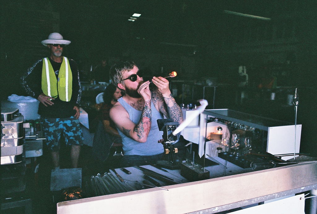 Jake Zolie demonstrates his glass-blowing skills at the 1906 warehouse. 35mm film photo by Page Graham.