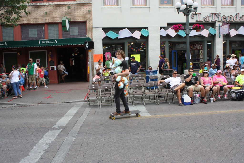A young vendor finds a solution to easy delivery by skateboarding his goods along the parade route. This scene was captured at the Battle of Flowers Parade, April 25, 2014. Photo by Kay Richter.