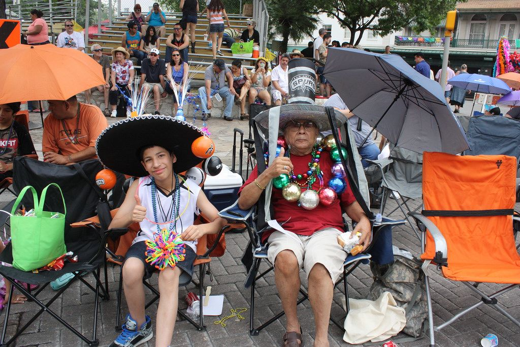 Two Fiesta revelers wait for the parade to begin, sitting in the comfort of their lawn chairs. Many revelers could be seen in similar scenes at the Battle of Flowers Parade, April 25, 2014. Photo by Kay Richter.