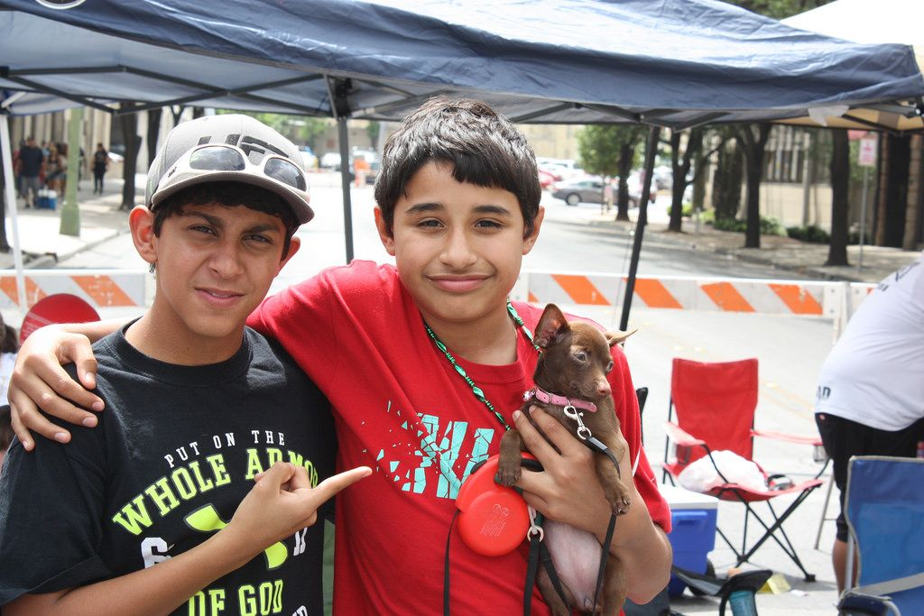 Two young boys pose for a quick photo with their chihuahua puppy named Cici while at the Battle of Flowers Parade, April 25, 2014. Photo by Kay Richter.