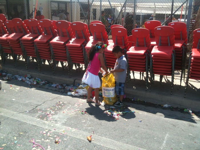 After a Fiesta parade in 2012, two young San Antonians help pick up trash. Photo courtesy of Keep San Antonio Beautiful.