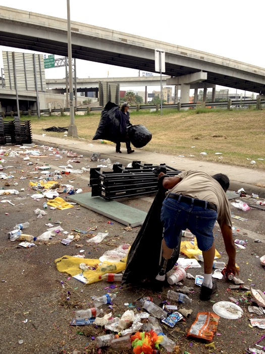 Workers pick up cans along Broadway the morning after the Fiesta Flambeau. Photo by Robert Rivard