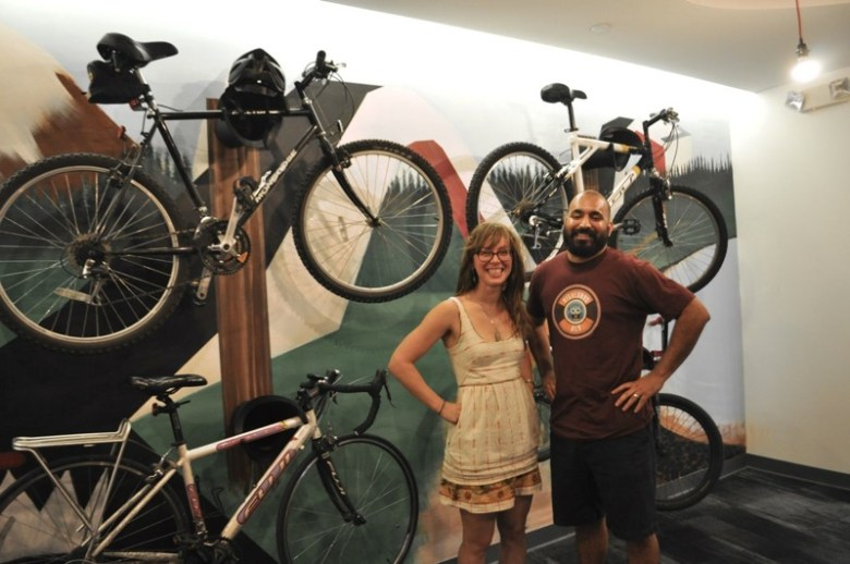 Geekdom Community Manager Julie Campbell poses for a photo with 80/20 Foundation Executive Director Lorenzo Gomez in front of the new Geekdom bike rack and mural in the co-working space's lobby. Photo by Iris Dimmick.