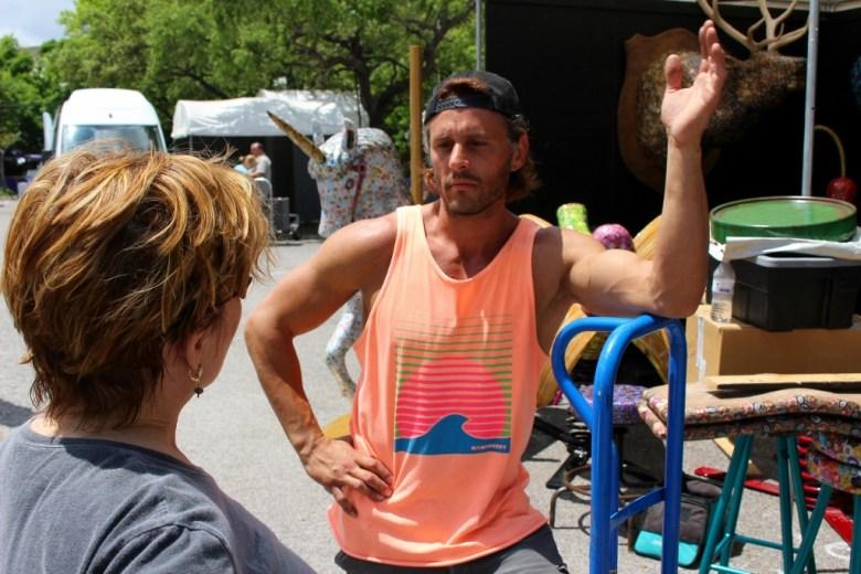 Dakota Pratt takes a break from setting up his work to talk to Tami Kegley. Photo by Page Graham.
