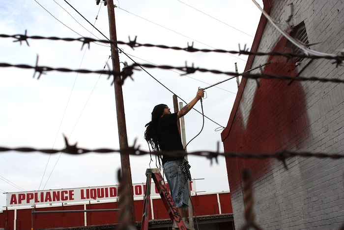Nik Soupe, a local graffiti artist and organizer, applies a primer to one of the exterior wall of The Appliance Warehouse that will be used for the weekend's graffiti festival. Photo by Kay Richter.