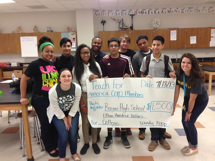 Alexander George and his colleagues present a check to several students at Reagan High School. George and several other TFA teachers raised $1,500 in under two weeks for Reagan students' college scholarships. Courtesy photo.