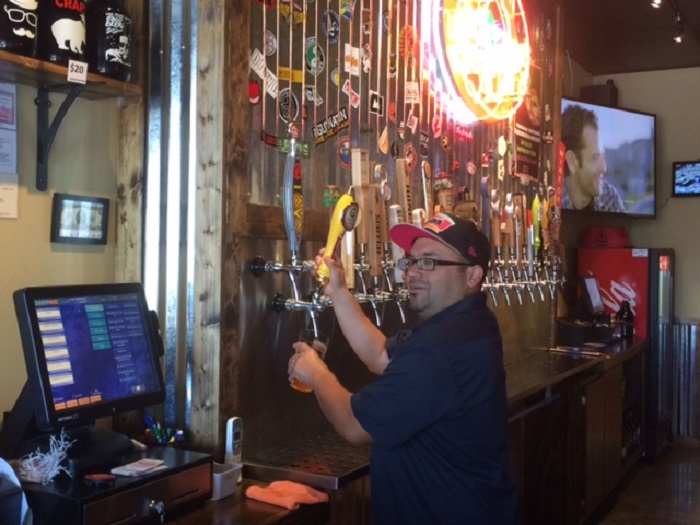 Augie serves up a Redfish IPA from Goliad Brewery at Big Hops Growlers on Huebner Road. Photo by Chris Day.